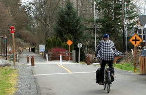 A cyclist heads from paved to gravel section of East Lake Sammamish Trail.