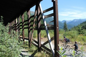 Cyclists pass snow shed on John Wayne Pioneer Trail