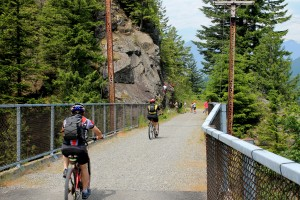 Cyclists pass rock climbers on John Wayne Pioneer Trail